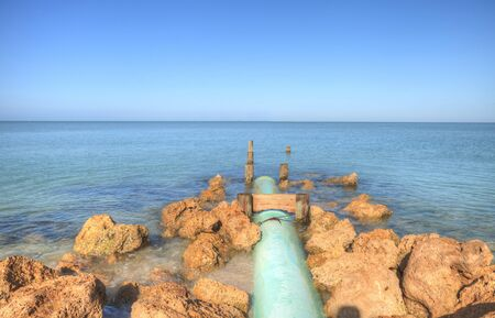 Drainage pipe leads into the ocean at Lowdermilk Beach in Naples, Florida