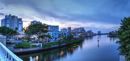 Pink Sunset over the colorful shops of the Village on Venetian Bay in Naples, Florida