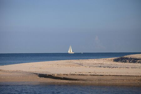 Sailboat glides across the bright blue ocean in Gulf Coast of Florida