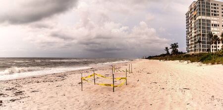 Dark sky over fenced off turtle nest on Clam Pass Beach in Naples, Florida