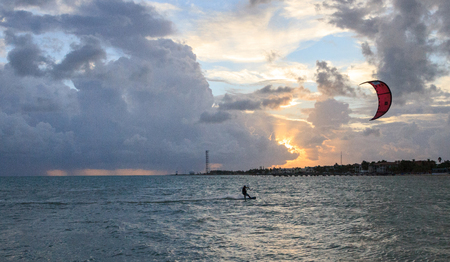 Silhouette of a Kite surfer in the ocean along the coast of southern Florida at sunset.