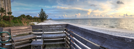 Bench overlooks the ocean at Vanderbilt Beach at sunset in Naples, Florida Stock Photo