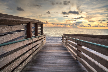 Boardwalk leading to the ocean at Vanderbilt Beach at sunset in Naples, Florida