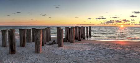 Dilapidated ruins of a pier on Port Royal Beach at sunset in Naples, Florida