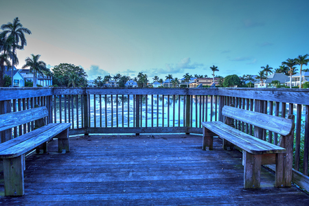 Secluded benches on a small deck overlooking a pond in Naples, Florida.
