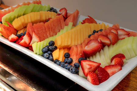 Fresh fruit platter including watermelon, cantaloupe, honeydew melon, strawberries, pineapple, and blueberries.