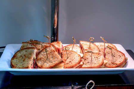 Grilled Reuben sandwich made with corned beef, sauerkraut and Swiss cheese on rye bread at a buffet. Stock Photo