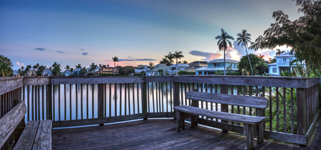 Sunset over a secluded benches on a small deck overlooking a pond in Naples, Florida. Stock Photo