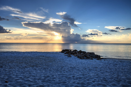 Sunset over the white sand on Naples Beach in Naples, Florida in summer.