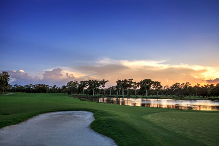 Golden pond at sunset at a golf course on a tropical island right near a sand trap. Stock Photo