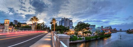 Christmas lights glow at Sunset over the colorful shops of the Village on Venetian Bay in Naples, Florida.
