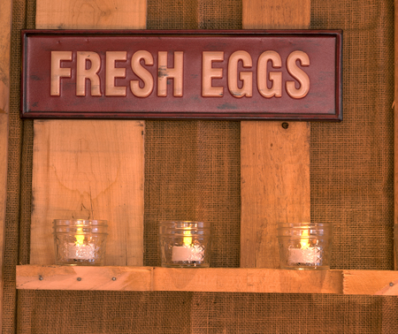 Red classic antique sign that says Fresh Eggs on a wood background with candles glowing below.