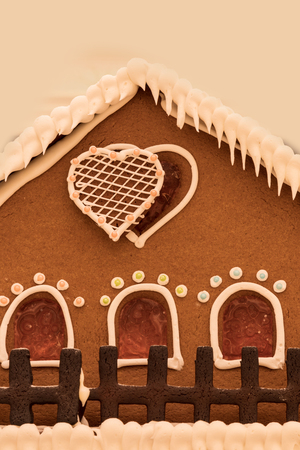 Gingerbread house with white icing and heart shaped windows with gingerbread trees and white frosting made to look like snow.