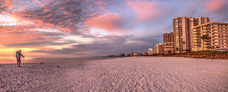 Old man at sunset with a pink and golden sky over South Marco Island Beach in Florida Stock Photo