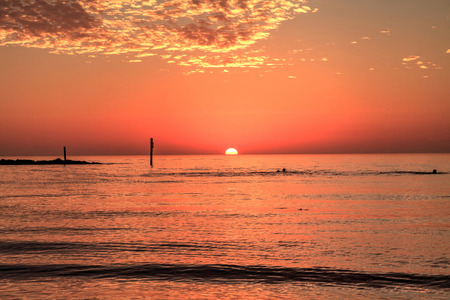 Swim at sunset with a red sky over South Marco Island Beach in Florida