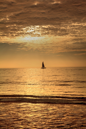 Sailboat against the golden sky of South Marco Island Beach at Sunset in Florida