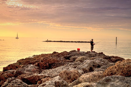 Fisherman on the rocks of South Marco Island Beach at Sunset with a boat in the distance in Florida