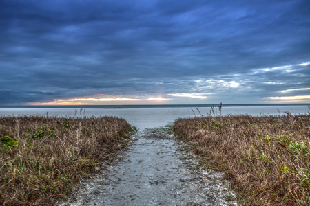 White sand path leading through the beach grass at Tigertail Beach at sunset on Marco Island, Florida. Banque d'images