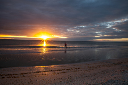 Man fishes along Tigertail Beach at sunset on Marco Island, Florida