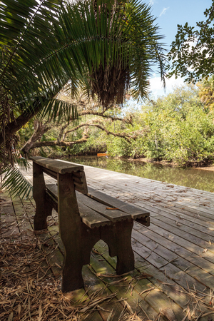 Estero, Florida, USA - February 23, 2019:  Old dock and bench along the riverway at historic Koreshan State Park. 免版税图像