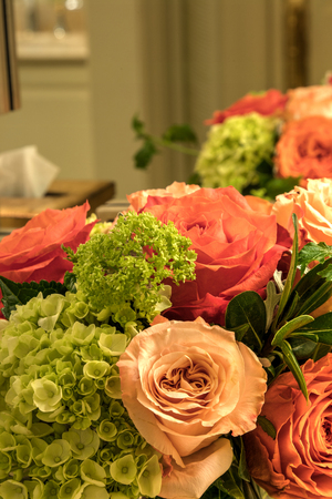 Pale bouquet of pink, orange and white roses with green hydrangea flowers.