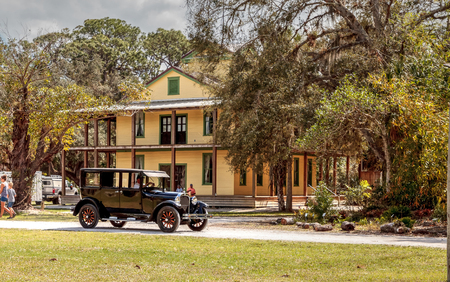 Estero, Florida, USA - February 23, 2019:  Black 1929 Dodge Brothers Model B drives in front of the 1929 Planetary Court at the 10th Annual Classic Car and Craft Show at historic Koreshan State Park.