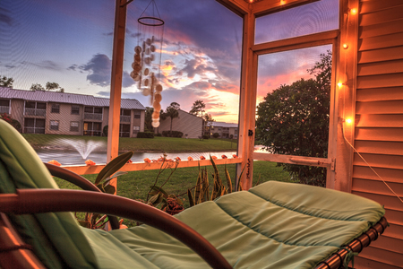 Swinging lounge chair on a lanai at sunset as it overlooks a pond with a fountain with golden light filtering into the patio. Stock Photo