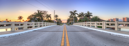 Bridge roadway over a riverway that leads to the ocean on Marco Island, Florida at Sunrise.