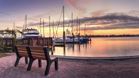 Break of dawn sunrise over boats and sailboats at Factory Bay marina in Marco Island, Florida