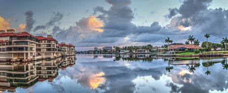 Sunrise at a waterway of Venetian Bay in Naples, Florida at sunrise. 免版税图像