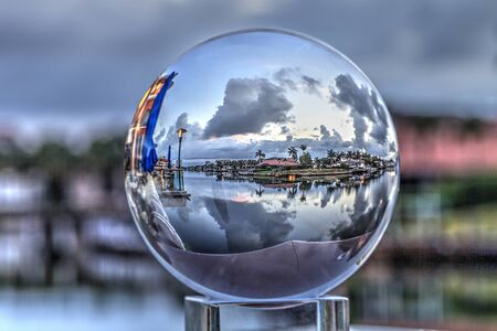 Crystal ball view of Sunrise at a waterway of Venetian Bay in Naples, Florida at sunrise. 免版税图像