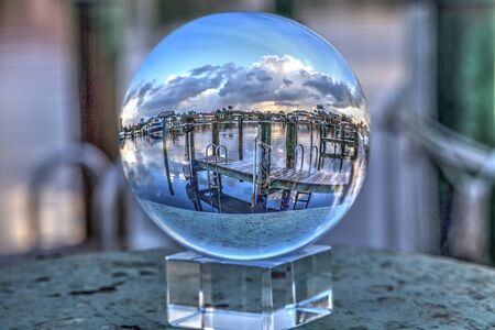 Crystal ball of Boats docked at a Marina near Venetian Bay in Naples, Florida at sunrise. 免版税图像