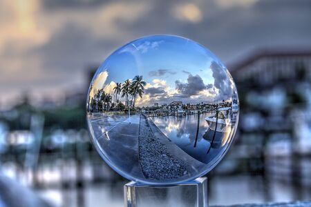 Crystal ball of Boats docked at a Marina near Venetian Bay in Naples, Florida at sunrise.