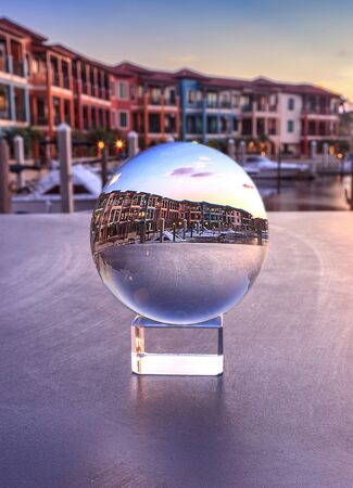 Naples, Florida, USA – May 29, 2019: Crystal ball with colorful buildings and a harbor of boats along a waterway in Naples, Florida inside.