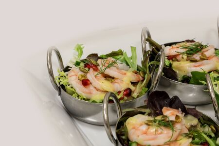Shrimp, spring greens, pomegranate salad with citrus dressing at a lunch buffet.