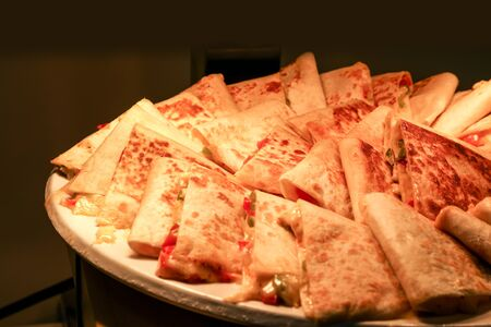 Quesadilla slices with cheese under a heat lamp at a lunch buffet Stock Photo