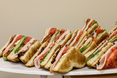 Club sandwich with turkey, bacon, tomato and bread laid out at a lunch buffet.