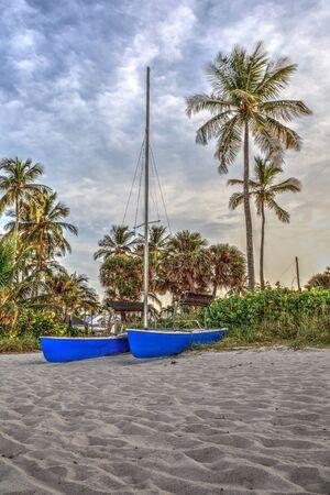 Catamaran boat at sunrise on a white sand beach in Southern Florida. 版權商用圖片