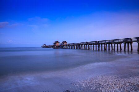 Amanecer sobre el muelle de Naples, donde la gente pesca al amanecer en Naples, Florida.
