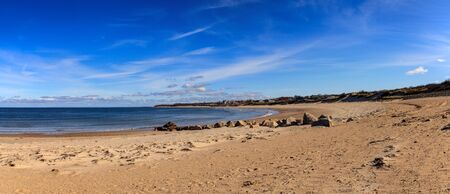 Blue skies over Corporation Beach in Dennis, Massachusetts on Cape Cod in the fall. 免版税图像