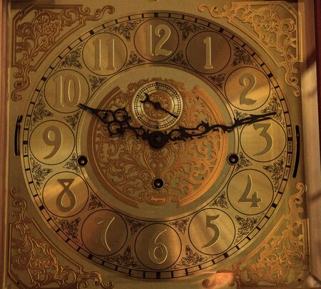 Old fashioned ornate grandfather clock at 10:13 with a gold brass face and black hands.