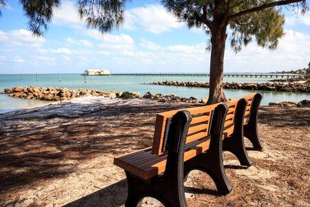 Bench overlooks the Anna Maria Island City pier on Anna Maria island, Florida. Фото со стока
