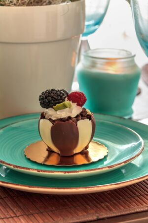 White and dark chocolate mousse dessert with whipped cream and fruit on top.