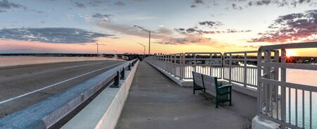 Bench view of a Golden sunset the SS Jolley Bridge into Marco Island, Florida.