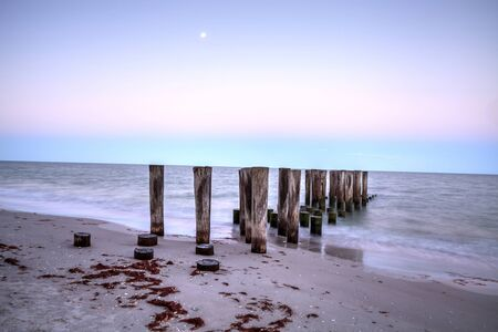Dilapidated pier leading into the ocean on the beach of Port Royal in Naples, Florida at sunrise as the full moon sets.