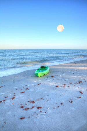 Green kayak on the white sand of Tigertail Beach in Marco Island, Florida as the full moon sets.