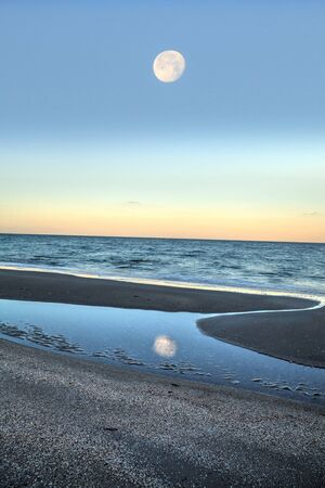 Reflection of the full moonset in a tidal pool in front of the ocean on Naples Beach in Naples, Florida at sunrise. Stock Photo