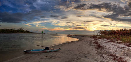 Paddleboard on white sand at sunset as clouds hang over Barefoot Beach in Bonita Springs, Florida. 스톡 콘텐츠