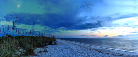 Moonrise over the dark sky over Barefoot Beach in Bonita Springs, Florida
