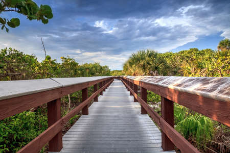 Boardwalk leads down to the white sand of Barefoot Beach in Bonita Springs, Florida 스톡 콘텐츠